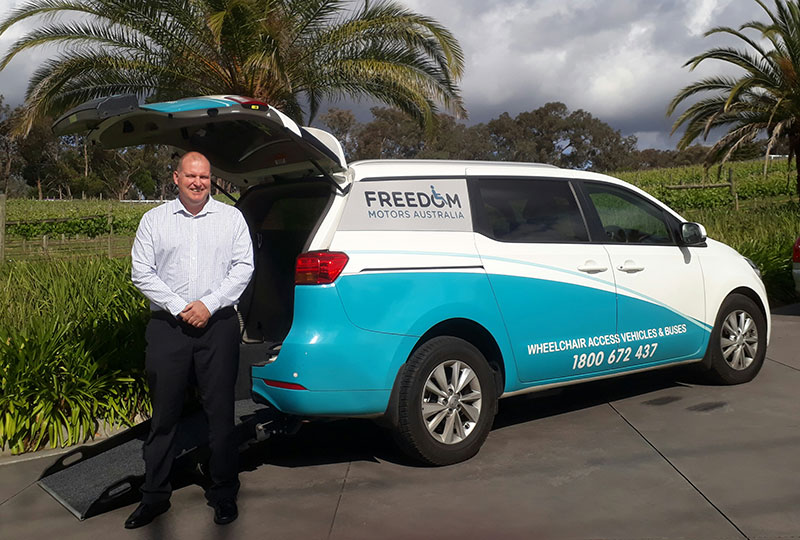 Our friendly Melbourne Victoria Sales manager Craig Speirs standing in front of a converted freedom access van which allows for people with wheelchairs access and passage to ride along with other passengers, Victoria located Freedom Motors Australia business.
